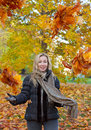 The young attractive woman with a long fair hair in autumn park among bright leaves of trees in a sunny day beautiful throws up Royalty Free Stock Photography
