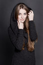 Young attractive woman with long gorgeous dark blond hair and large blue eyes she is dressed in warm gray knit dress a hood Stock Images