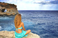 Young attractive woman looking at sea horizon sitting alone on r Royalty Free Stock Photo