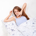 Young attractive woman lying in bed yawing Royalty Free Stock Image