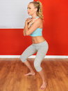 Young attractive woman performing exercise squats with blonde hair in her twenties or doing a series of bending her knees with her Stock Photography