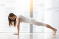Young attractive woman in Plank pose against floor window Royalty Free Stock Photo