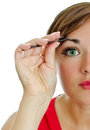 Young attractive woman plucking her eyebrows Royalty Free Stock Image