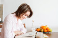Young attractive woman reading a book at home having fruits an eating and drinking coffee Royalty Free Stock Photography