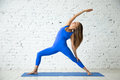 Young attractive woman in Reverse Warrior pose, white studio bac Royalty Free Stock Photo