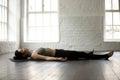 Young attractive woman in Savasana pose, white loft studio backg