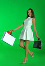 Young attractive woman with shopping bags posing against a removable green chroma key background Stock Image