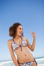 Young attractive woman standing on the beach while pointing her Stock Photo