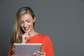 Young attractive woman using a tablet computer smiling on gray background Royalty Free Stock Photos