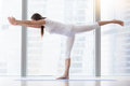 Young attractive woman in Virabhadrasana III pose against floor Royalty Free Stock Photo