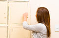 Young attractive woman wearing grey sweater opening metal locker door, rack of lockers stacked Royalty Free Stock Photo