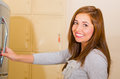 Young attractive woman wearing grey sweater smiling and opening metal locker door, rack of lockers stacked Royalty Free Stock Photo