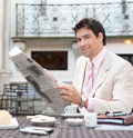 Young atttactive hispanic businessman reading newspaper having breakfast coffee shop terrace classic city Royalty Free Stock Photos