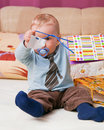 Young baby boy with a dummy in his mouth playing colorful gift bags Royalty Free Stock Photo