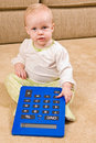 Young baby in pjs with a large over sized calculat pair of generic sitting on living room floor calculator she is looking forward Royalty Free Stock Image