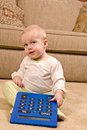 Young baby in pjs with a large over sized calculator pair of generic sitting on living room floor she is looking up and to Stock Images