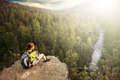 Young backpacker looking into the distance from mountain peak woman with backpack look at green forest and river high point of Stock Images