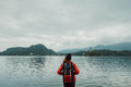 Young backpacker woman standing by mountain lake with backpack Royalty Free Stock Photo