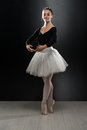 Young ballerina dancer in tutu performing on pointes beautiful female ballet a black background is wearing a and pointe shoes Royalty Free Stock Images