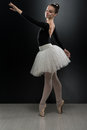 Young ballerina dancer in tutu performing on pointes beautiful female ballet a black background is wearing a and pointe shoes Royalty Free Stock Photo
