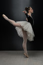 Young ballerina dancer in tutu performing on pointes beautiful female ballet a black background is wearing a and pointe shoes Royalty Free Stock Photos
