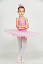 Young ballerina girl in a pink dress on a light background Royalty Free Stock Photo