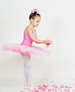 Young ballerina girl in a pink dress on a light background Stock Image