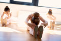 Young ballerinas doing stretching exercises group of in class seated on the wooden floor as they warm up before practice to Royalty Free Stock Photography