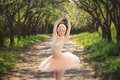 Young ballet dancer showing classic ballet poses outdoors at sun
