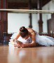 Young ballet dancer stretching on dance floor Stock Photos