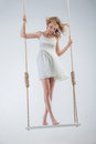 Young bare-footed girl on swing looking down. Royalty Free Stock Photo