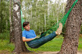 Young barefooted man in glasses with reclines in hammock Royalty Free Stock Photo