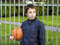 Young basketball player holding ball against iron fence at the playground Royalty Free Stock Photos