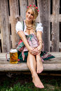 Young bavarian oktoberfest blonde woman in a dirndl dress with beer