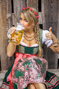 Young bavarian oktoberfest blonde woman in a dirndl dress with beer Royalty Free Stock Photo