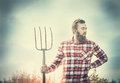 Young bearded farmer in red checkered shirt with old pitchfork sky  nature backgrund, toned Royalty Free Stock Photo