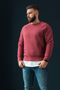 A young bearded handsome male hipster, dressed in a red pullover with long sleeves and jeans, stands indoors.