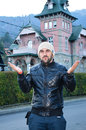 Young bearded handsome man sending kisses on background of beautiful old pink house in the mountain with hat and leather jacket Stock Photo