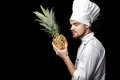 Young bearded man chef In white uniform holds Fresh pineapple on black background Royalty Free Stock Photo