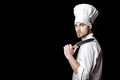 Young bearded man chef In white uniform holds  knife on  black background Royalty Free Stock Photo