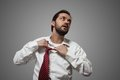 Young bearded man removing his red tie grey background Royalty Free Stock Photo