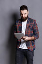Young bearded man using tablet computer Royalty Free Stock Photo