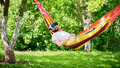 Young bearded man wearing virtual reality goggles relaxing in a garden hammock. Lifestyle VR fun and relax Royalty Free Stock Photo