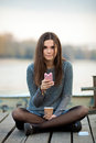 Young beautful brunette woman using her smartphone outdoors in sweater and denim skirt sitting on the river pier with coffee and Royalty Free Stock Photos