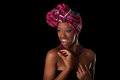 Young beautiful african woman wearing a traditional headscarf i isolated over black background Royalty Free Stock Image