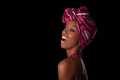 Young beautiful african woman wearing a traditional headscarf i over black background Stock Image