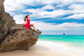 Young beautiful alone woman in red dress sitting on the rock sea backgound Stock Photos