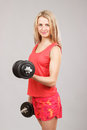 Young beautiful athletic girl holding dumbbells Royalty Free Stock Photo