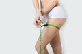 Young beautiful athletic girl measures thighs and legs measuring tape, healthy lifestyle, fitness, exercise, healthy slim body Royalty Free Stock Photo