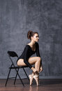 Young and beautiful ballerina sitting on a chair in a point shoes Royalty Free Stock Photo